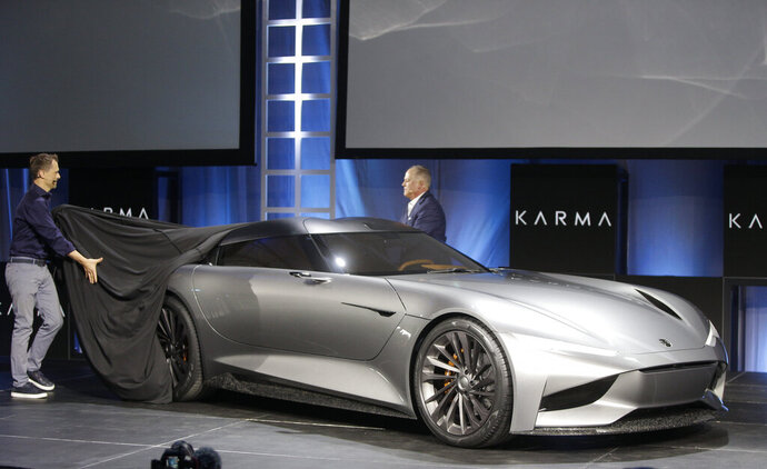CORRECTS VEHICLE TO KARMA SC2 CONCEPT INSTEAD OF KARMAN VISION SC2  - Karma Automotive Andreas Thurner, Vice President for Global Design and Architecture, left, and Todd George, VP of Platform Engineering at Karma Automotive, unveil the Karma SC2 concept vehicle at the Automobility LA Auto Show in Los Angeles Tuesday, Nov. 19, 2019. (AP Photo/Damian Dovarganes)