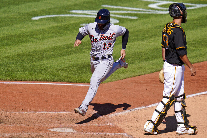 Detroit Tigers' Eric Haase (13) scores past Pittsburgh Pirates catcher Jacob Stallings on a sacrifice fly by Miguel Cabrera off Pirates starting pitcher Bryse Wilson during the sixth inning of a baseball game in Pittsburgh, Monday, Sept. 6, 2021. (AP Photo/Gene J. Puskar)