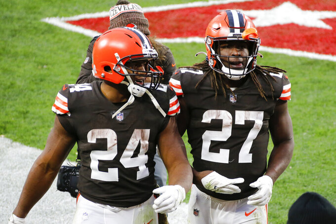 File-This Nov. 15, 2020, file photo shows Cleveland Browns running backs Nick Chubb (24) and Kareem Hunt (27) walking off the field after the Browns defeated the Houston Texans in Cleveland. One is quiet, super steady, and a rising NFL star. Cleveland's other running back is outgoing, flashy, and has his career back on track after a major detour. Chubb and Hunt couldn't be any different. (AP Photo/Ron Schwane, File)