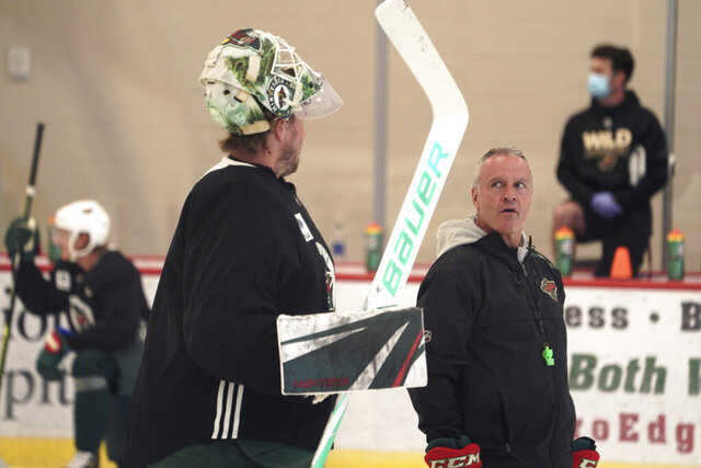 Minnesota Wild coach Dean Evason talks with goalie Devan Dubnyk before practice at the NHL hockey team's training camp Monday, July 13, 2020, in St. Paul, Minn., after a break in the season because of the coronavirus pandemic. (Brian Peterson/Star Tribune via AP)