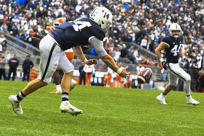 Penn State quarterback Sean Clifford (14) reaches for an incomplete pass from tight end Tyler Warren (44) in the third overtime of an NCAA college football game against Illinois in State College, Pa., Saturday, Oct. 23, 2021. Illinois defeated Penn State 20-18 in the ninth overtime. (AP Photo/Barry Reeger)