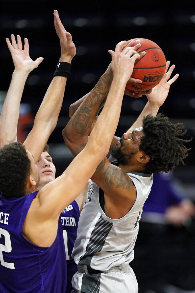 Chicago State forward Aaris-Monte Bonds, right, shoots against Northwestern forward Robbie Beran and forward Pete Nance during the first half of an NCAA college basketball game in Evanston, Ill., Saturday, Dec. 5, 2020. (AP Photo/Nam Y. Huh)