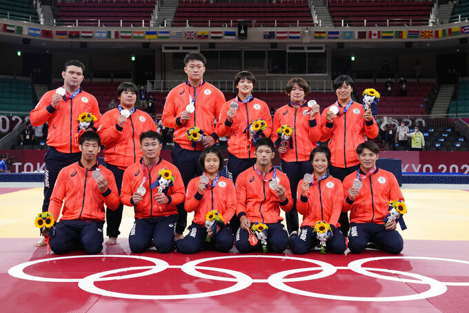 Members of Japan's team pose with their silver medals after the medal ceremony in team judo competition at the 2020 Summer Olympics, Saturday, July 31, 2021, in Tokyo, Japan. (AP Photo/Vincent Thian)