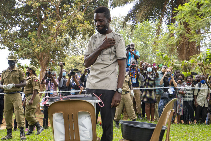 Uganda's leading opposition challenger Bobi Wine makes the sign of the cross after voting in Kampala, Uganda, Thursday, Jan. 14, 2021. Ugandans are voting in a presidential election tainted by widespread violence that some fear could escalate as security forces try to stop supporters of Wine from monitoring polling stations.(AP Photo/Jerome Delay)