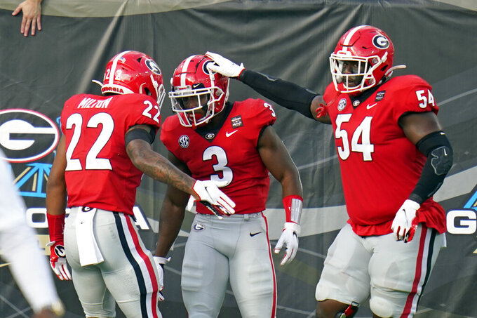 Georgia running back Zamir White (3) celebrates his 75-yard touchdown run with running back Kendall Milton (22) and offensive lineman Justin Shaffer (54) during the first half of an NCAA college football game against Florida, Saturday, Nov. 7, 2020, in Jacksonville, Fla. (AP Photo/John Raoux)