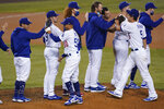 Los Angeles Dodgers right fielder Mookie Betts (50), shortstop Corey Seager (5) and teammates celebrate after the Dodgers clinched the NL West title with a 7-2 win over the Oakland Athletics in a baseball game Tuesday, Sept. 22, 2020, in Los Angeles. (AP Photo/Ashley Landis)
