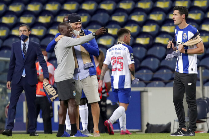 Porto former goalkeeper Iker Casillas, center with hat, celebrates with the players on the pitch at the end of the Portuguese League soccer match between FC Porto and Sporting CP at the Dragao stadium in Porto, Portugal, Wednesday, July 15, 2020. Porto defeated Sporting 2-0 to clinch the championship with two rounds left to play. (AP Photo/Luis Vieira)
