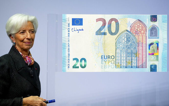 The new President of the European Central Bank Christine Lagarde adds her signature to an oversize euro banknote at the ECB in Frankfurt, Germany, Wednesday, Nov. 27, 2019. (AP Photo/Michael Probst)