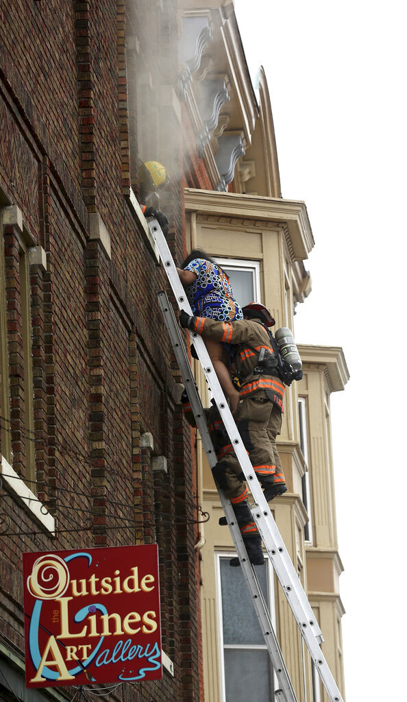 Emergency personnel rescue a woman from a building at the corner West 11th and Main streets in Dubuque, Iowa, on Monday, Jan. 27, 2020. Authorities say firefighters rescued four people from a fire that erupted in a downtown Dubuque building. (Jessica Reilly/Telegraph Herald via AP)
