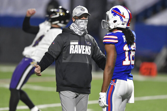 Baltimore Ravens coach John Harbaugh, center, talks to Buffalo Bills' Andre Roberts (18) before an NFL divisional round football game Saturday, Jan. 16, 2021, in Orchard Park, N.Y. (AP Photo/Adrian Kraus)