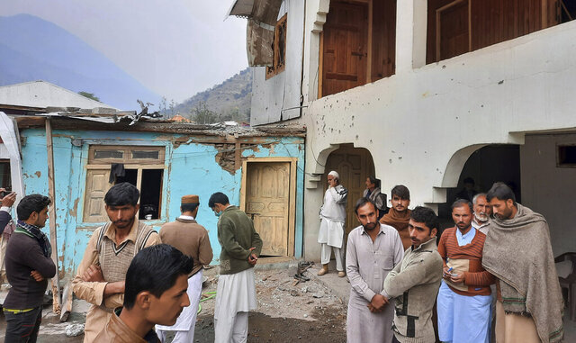 Local residents gather in a partially damage house caused by shelling of Indian forces at a village in Neelum Valley, situated at the Line of Control in Pakistan-administered Kashmir, Friday, Nov. 13, 2020. Pakistani and Indian troops clashed in disputed Kashmir, leaving few people dead and wounding more than 30 others on both sides, officials said Friday. The fighting came amid increasing tension between the South Asian neighbors. (AP Photo/Nisar Mughal)