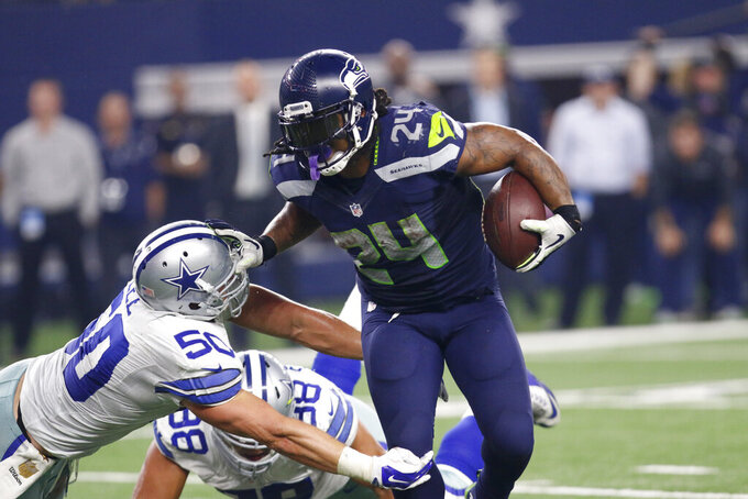 FILE - In this Nov. 1, 2015, file photo, Dallas Cowboys outside linebacker Sean Lee (50) defends against a run by Seattle Seahawks running back Marshawn Lynch (24) during an NFL football game in Arlington, Texas. The Seahawks could be reuniting with former star running back Lynch, coach Pete Carroll said during his radio show Monday, Dec. 23, 2019. Carroll said Lynch is flying to Seattle and will undergo a physical later Monday. Seattle is in desperate need of running backs after Chris Carson (hip) and C.J. Prosise (arm) both suffered season-ending injuries in Sunday's 27-13 loss to Arizona. (AP Photo/Roger Steinman, File)