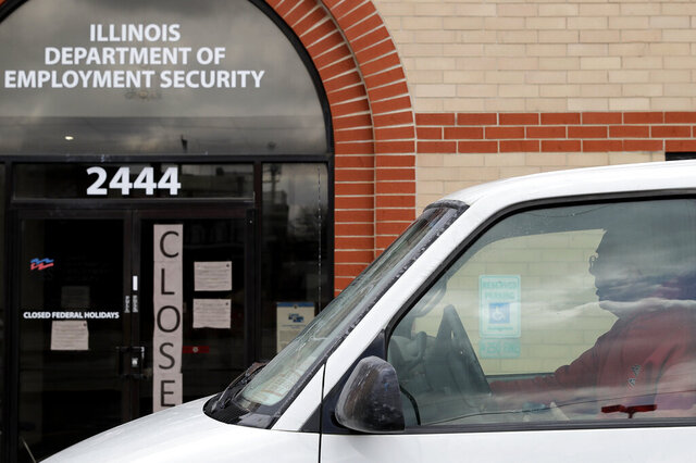 A man looks at the closed sign in front of Illinois Department of Employment Security in Chicago, Wednesday, April 15, 2020. With half-a-million people bounced out of jobs in the past month because of the COVID-19 pandemic, Illinois' unemployment safety net has been stretched to the limit. (AP Photo/Nam Y. Huh)