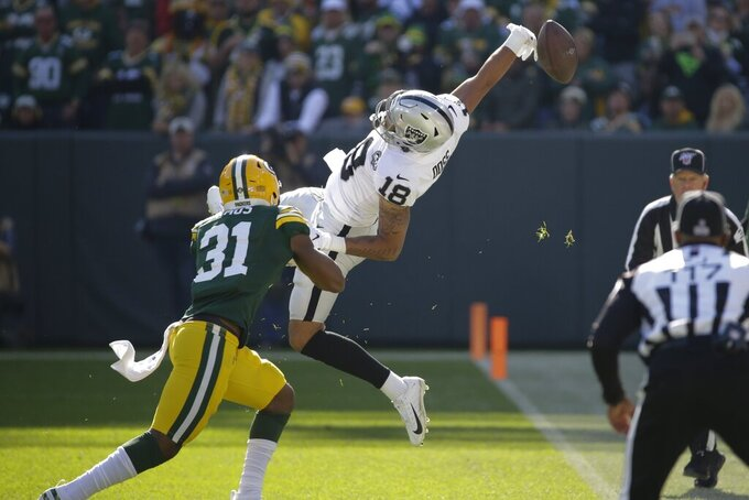 Oakland Raiders' Keelan Doss can't catch a pass in front of Green Bay Packers' Adrian Amos can't catch during the first half of an NFL football game Sunday, Oct. 20, 2019, in Green Bay, Wis. (AP Photo/Mike Roemer)