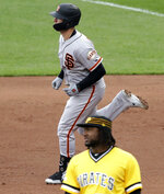 San Francisco Giants' Buster Posey, rear, rounds first base behind Pittsburgh Pirates' Josh Bell after hitting a three-run home run off Pittsburgh Pirates starting pitcher Chris Archer in the fifth inning of a baseball game in Pittsburgh, Sunday, April 21, 2019. (AP Photo/Gene J. Puskar)
