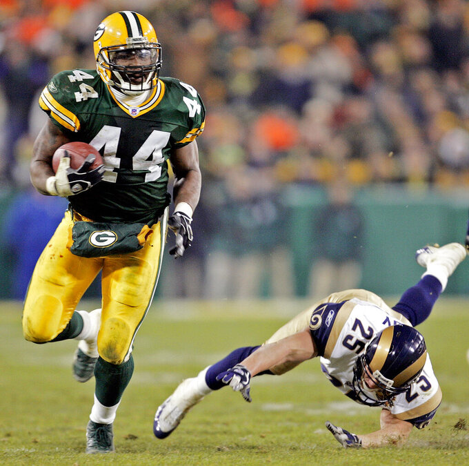 """File-Green Bay Packers' Najeh Davenport breaks away from St. Louis Rams' Rich Coady (25) for a 40-yard touchdown run in the fourth quarter Monday, Nov. 29, 2004, in Green Bay, Wis. Dementia tests in the NFL concussion litigation allow doctors to use different baseline standards for Black and white retired players, making it more difficult for Blacks to show injury and qualify for awards, lawyers for two ex-players argued in court filings Tuesday, Aug. 25, 2020.  Lawyers for ex-players Kevin Henry and Davenport said their clients were denied awards """"based on a discriminatory testing regime"""" that weighs sociological factors including race. Both men would have qualified for awards had race not been considered, they said. (AP Photo/Morry Gash, File)"""