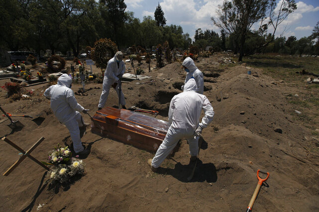 Cemetery workers in a protective gear lower a coffin wrapped in plastic, containing a COVID-19 victim, into a gravesite at the San Lorenzo Tezonco Iztapalapa cemetery in Mexico City, Tuesday, June 2, 2020. The coronavirus toll in Mexico soared to a new daily high Wednesday, more than double the previous one-day record. (AP Photo/Marco Ugarte)