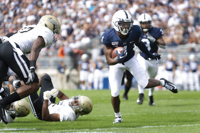 Penn State wide receiver K.J. Hamler, right, looks to elude Idaho defensive back Tyrese Dedmon, left, during the first quarter of an NCAA college football game in State College, Pa., on Saturday, Aug. 31, 2019. (AP Photo/Barry Reeger)
