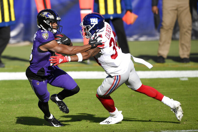 Baltimore Ravens' Devin Duvernay, left, returns the opening kickoff as New York Giants' Adrian Colbert tries to stop him during the first half of an NFL football game, Sunday, Dec. 27, 2020, in Baltimore. (AP Photo/Nick Wass)