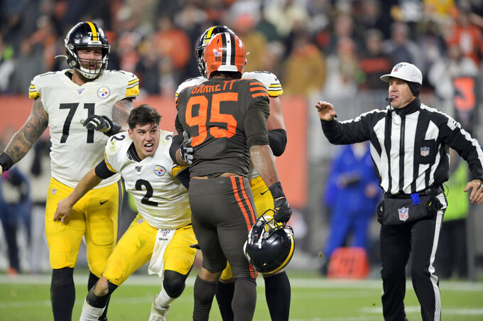 Pittsburgh Steelers quarterback Mason Rudolph (2) goes after Cleveland Browns defensive end Myles Garrett (95) during the second half of an NFL football game, Thursday, Nov. 14, 2019, in Cleveland. (AP Photo/David Richard)