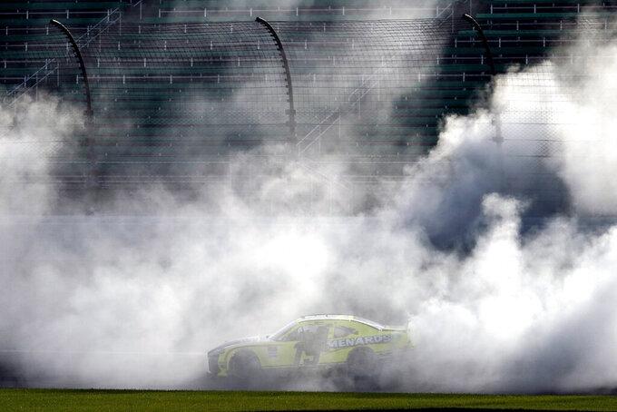 Brandon Jones does a burnout after winning a NASCAR Xfinity Series auto race at Kansas Speedway in Kansas City, Kan., Saturday, July 25, 2020. (AP Photo/Charlie Riedel)