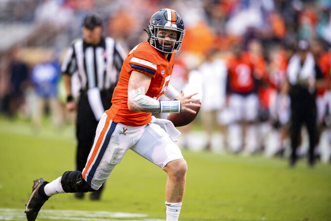 Virginia quarterback Brennan Armstrong (5) scrambles out of the pocket during the second quarter of an NCAA college football game against Duke at Scott Stadium on Saturday, Oct. 16, 2021, in Charlottesville, Va. (AP Photo/Mike Caudill)