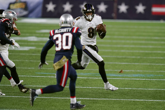 Baltimore Ravens quarterback Lamar Jackson tries to run away from New England Patriots cornerback Jason McCourty (30) in the first half of an NFL football game, Sunday, Nov. 15, 2020, in Foxborough, Mass. (AP Photo/Charles Krupa)