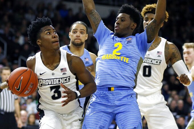 Providence's David Duke (3) looks to shoot against Marquette's Sacar Anim (2) during the first half of an NCAA college basketball game in Providence, R.I., Saturday, Feb. 23, 2019. (AP Photo/Michael Dwyer)