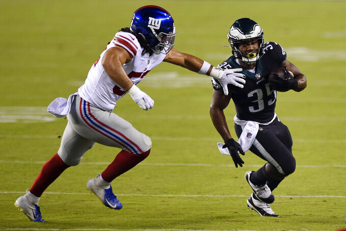 Philadelphia Eagles' Boston Scott, right, tries to slip past New York Giants' Devante Downs during the first half of an NFL football game, Thursday, Oct. 22, 2020, in Philadelphia. (AP Photo/Derik Hamilton)