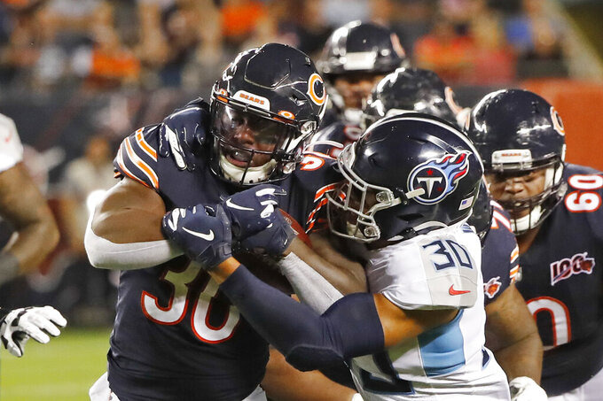 Chicago Bears running back Josh Caldwell, left, is tackled by Tennessee Titans defensive back LaDarius Wiley, right front, during the first half of an NFL preseason football game Thursday, Aug. 29, 2019, in Chicago. (AP Photo/Charles Rex Arbogast)