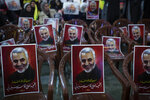 Posters of slain Iranian Revolutionary Guard Gen. Qassem Soleimani are placed on chairs as supporters of Hezbollah leader Sayyed Hassan Nasrallah gather for his televised speech in a southern suburb of Beirut, Lebanon, Sunday, Jan. 5, 2020 following the U.S. airstrike in Iraq that killed Soleimani. The posters read: