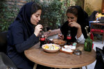 Two Iranians drink Coca-Cola at a cafe in downtown Tehran, Iran, Wednesday, July 10, 2019. Whether at upscale restaurants or corner stores, American brands like Coca-Cola and Pepsi can be seen throughout Iran despite the heightened tensions between the two countries. U.S. sanctions have taken a heavy toll, but Western food, movies, music and clothing are still widely available. (AP Photo/Ebrahim Noroozi)