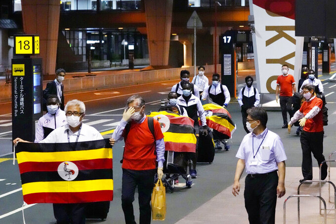 Members of Uganda's Olympic team prepare to leave for Osaka, at Narita Airport in Narita, near Tokyo early Sunday June 20, 2021. A member of the team has tested positive for the coronavirus and was barred entry into Japan, in the first detected infection among arriving athletes for the Tokyo Games opening in five weeks. (Sadayuki Goto/Kyodo News via AP)
