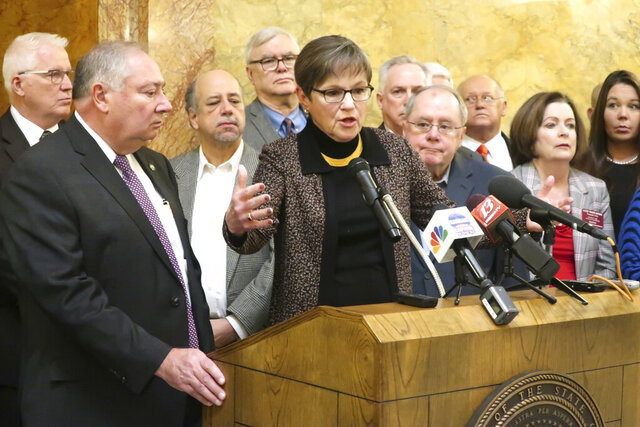 Kansas Gov. Laura Kelly, center, answers questions from reporters about a new Medicaid expansion plan as lawmakers and other advocates watch, including Senate Majority Leader Jim Denning, second from the left, during a news conference, Thursday, Jan. 9, 2020, at the Statehouse in Topeka, Kansas. (AP Photo/John Hanna)