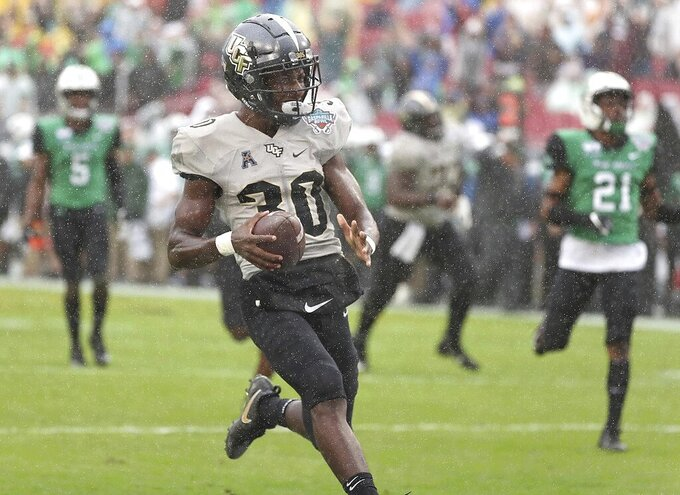 Central Florida running back Greg McCrae leaves Marshall defenders behind on a touchdown run during the Gasparilla Bowl NCAA college football game Monday, Dec. 23, 2019, in Tampa, Fla. (Stephen M. Dowell/Orlando Sentinel via AP)