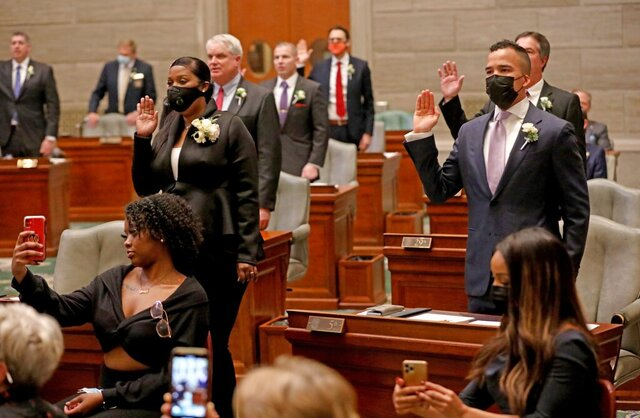 Democrats Angela Walton Mosley of Florissant, left, and Steven Roberts Jr. of St. Louis, right, raise their hands as they are sworn in as state senators on Wednesday, Jan. 6, 2021, at the Capitol in Jefferson City, Mo. (Laurie Skrivan/St. Louis Post-Dispatch via AP)
