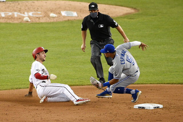 Washington Nationals' Trea Turner, left, is out as he tries to steal second base against Toronto Blue Jays shortstop Santiago Espinal (5) during the sixth inning of a baseball game, Tuesday, July 28, 2020, in Washington. The Blue Jays won 5-1. (AP Photo/Nick Wass)