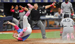 Home plate umpire Tony Randazzo, center, makes the call as Tampa Bay Rays pitcher Ryne Stanek, center, tumbles after trying to tag out New York Yankees' Luke Voit (45) in a collision at the plate during the eighth inning of a baseball game Sunday, May 12, 2019, in St. Petersburg, Fla. Voit scored on a wild pitch thrown by Stanek. (AP Photo/Steve Nesius)