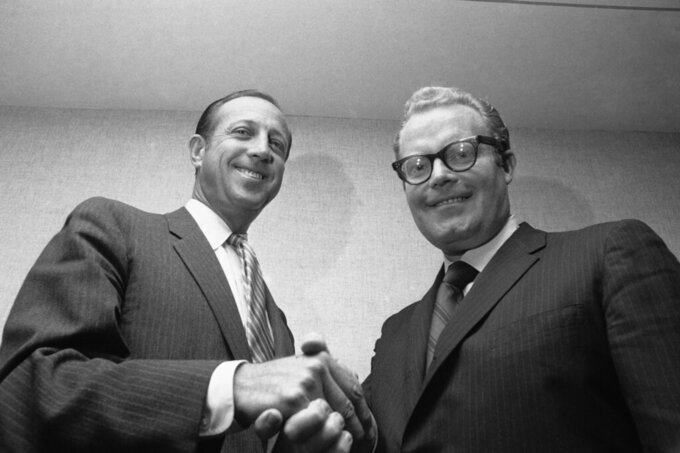 FILE - In this May 1969 file photo, NFL Commissioner Pete Rozelle, left, and Roone Arledge, president of ABC Sports, shake hands in New York, where it was announced that ABC would televise 13 regular-season games on Monday nights.  (AP Photo/File)