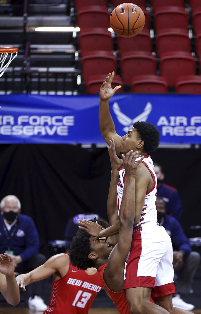 Fresno State guard Kyle Harding (0) shoots as New Mexico guard Saquan Singleton (2) defends during the second half of an NCAA college basketball game in the first round of the Mountain West Conference men's tournament Wednesday, March 10, 2021, in Las Vegas. (AP Photo/Isaac Brekken)