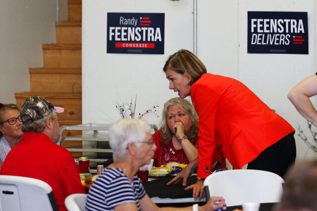 In this Aug. 7, 2020 photo provided by the Iowa Falls Times Citizen, Iowa Gov. Kim Reynolds greets people at the Hardin County GOP Sweet Corn Feed in Eldora, Iowa. Reynolds scoffs at calls for a statewide mask order, calling them