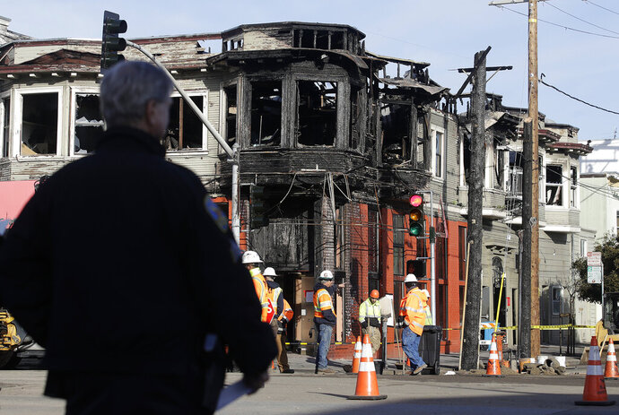 A San Francisco Police officer watches as a crew works at the scene of a Wednesday fire on Geary Boulevard in San Francisco, Thursday, Feb. 7, 2019. A gas explosion in shot a tower of flames into the sky and burned five buildings including one of the city's popular restaurants before firefighters brought the blaze under control. (AP Photo/Jeff Chiu)