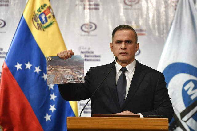 Venezuela's Attorney General Tarek William Saab holds a photo of bullets he says were seized with other weapons in connection with what the government calls a failed attack over the weekend aimed at overthrowing President Nicolás Maduro, during a press conference in Caracas, Venezuela, Friday, May 8, 2020. (AP Photo/Matias Delacroix)