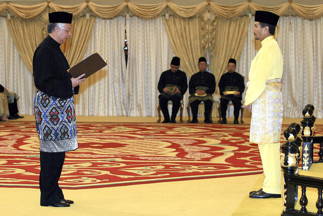 FILE - In this April 3, 2009, file photo Najib Razak, left, swears in as new Malaysian Prime Minister in front of Malaysian King Sultan Mizan Zainal Abidin at National Palace in Kuala Lumpur, Malaysia. Najib was found guilty Tuesday, July 28, 2020, in his first corruption trial over the multibillion-dollar looting of 1MDB. A massive financial scandal linked to the 1MDB wealth sovereign fund helped sink Najib's political career and ended the six-decade rule of his coalition in 2018 national elections. (Bernama via AP, File)