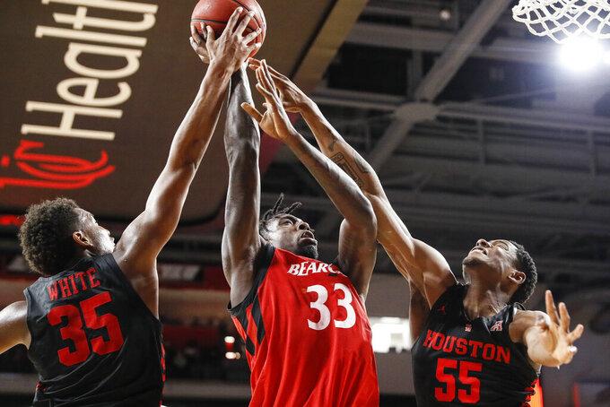 Cincinnati's Nysier Brooks (33) battles for the ball against Houston's Fabian White Jr. (35) and Brison Gresham (55) in the first half of an NCAA college basketball game Sunday, March 10, 2019, in Cincinnati. (AP Photo/John Minchillo)