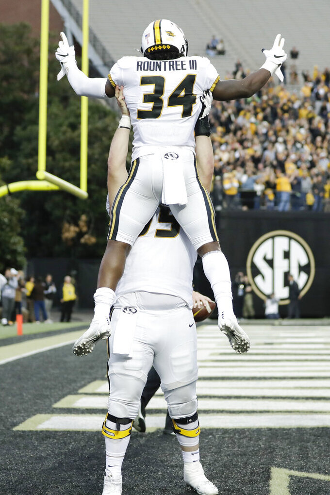 Missouri running back Larry Rountree III (34) celebrates with offensive lineman Trystan Colon-Castillo after Rountree scored a touchdown against Vanderbilt in the second half of an NCAA college football game Saturday, Oct. 19, 2019, in Nashville, Tenn. Vanderbilt upset Missouri 21-14. (AP Photo/Mark Humphrey)