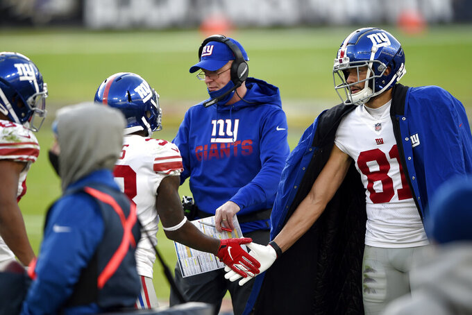 New York Giants offensive coordinator Jason Garrett, center, greets players on the sideline after a touchdown against the Baltimore Ravens during the second half of an NFL football game, Sunday, Dec. 27, 2020, in Baltimore. (AP Photo/Gail Burton)