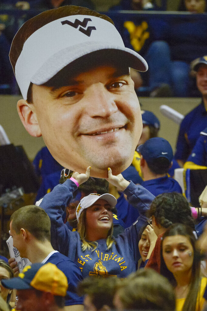 A Mountaineers fan holds aloft a large print cutout of the new WVU head football coach Neal Brown during the first half of an NCAA college basketball game in Morgantown, W.Va. on Saturday Feb. 9, 2019. (AP Photo/Craig Hudson)