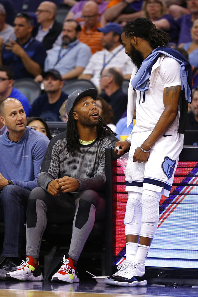 Arizona Cardinals Larry Fitzgerald, left, talks to Memphis Grizzlies guard Mike Conley (11) during the second half of the team's NBA basketball game against the Phoenix Suns, Saturday, March 30, 2019, in Phoenix. The Grizzlies won 120-115. (AP Photo/Rick Scuteri)