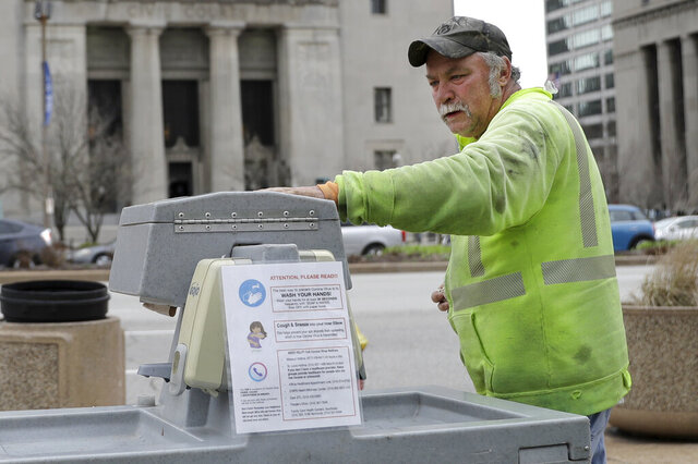 James Dundon with R&R Sanitation maintains a portable hand washing station Friday, March 20, 2020, in St. Louis. The stations have been placed around the city in an effort to slow the spread of the coronavirus. (AP Photo/Jeff Roberson)